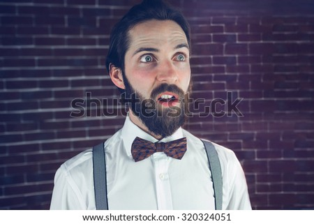 Confused man looking away against brick wall - stock photo