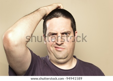 Confused man scratching head - stock photo