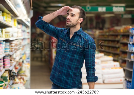 Confused Man Shopping At The Supermarket - stock photo