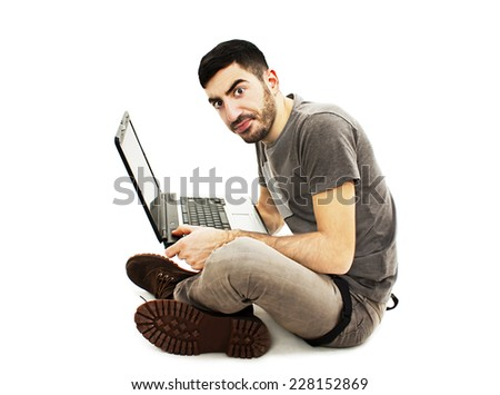 Confused man sitting on floor with laptop. Isolated on white background   - stock photo