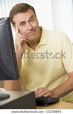 Confused man working on a computer - stock photo