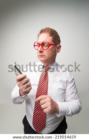 Confused middle-aged businessman looking at the smartphone - stock photo