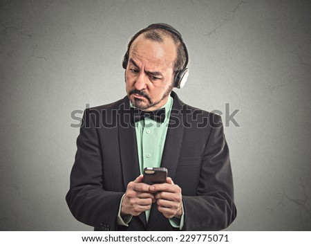 Confused middle aged man listening music with pair of headphones looking at his smartphone surprised. Closeup portrait man reading news on mobile phone isolated grey wall background. Face expression - stock photo