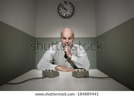 Confused office worker at his desk with intercoms.