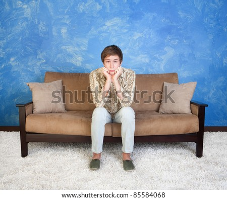 Confused or bored teen with hands on chin sits alone - stock photo