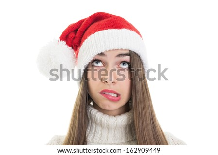Confused pretty Caucasian teenage girl wearing Santa beanie hat looking up making facial expression isolated on white background. Copy space available.  - stock photo
