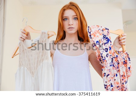 Confused pretty young woman standing at home and choosing clothes to wear  - stock photo