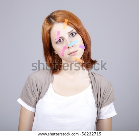 Confused red-haired businesswomen with notes on face. - stock photo