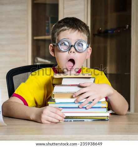Confused schoolboy in funny glasses screaming near the huge stack of books. Education. - stock photo