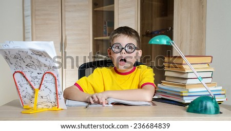 Confused schoolboy in funny glasses screaming near the huge stack of books. Education. Boy Having Problems With His Homework. - stock photo