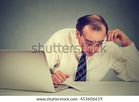 Confused surprised business man looking at documents. Shocked corporate middle aged executive working at his desk in office reviewing paperwork   - stock photo