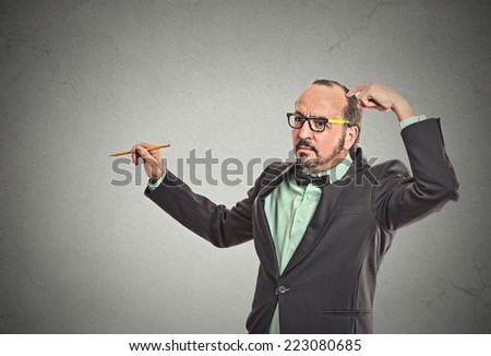 Confused teacher scratching his head thinking what to write on blackboard with copy space. Human face expressions, emotions, feelings, body language - stock photo
