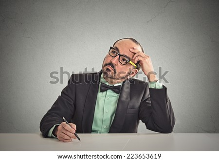 Confused teacher sitting at table scratching his head thinking what idea to write isolated office grey wall background with copy space. Human face expressions, emotions, feelings, body language - stock photo