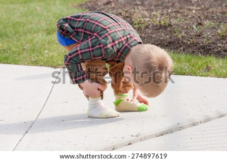 confused toddler dressed in two different socks looking and touching his feet outside on a sidewalk - stock photo