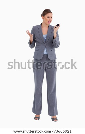 Confused tradeswoman looking at her cellphone against a white background
