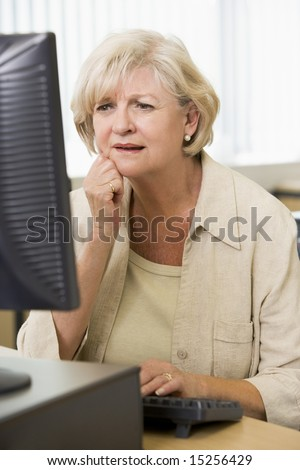 Confused woman frowning at computer monitor - stock photo