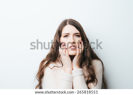 Confused woman puts her hands on the cheeks, isolated on white - stock photo