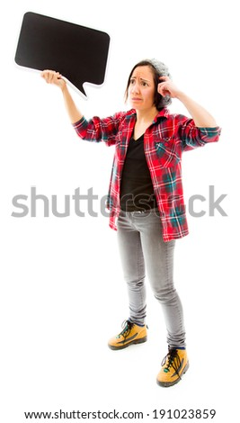 Confused woman with holding a blank speech bubble - stock photo