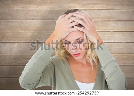 Confused young blonde with hands on head against wooden surface with planks - stock photo