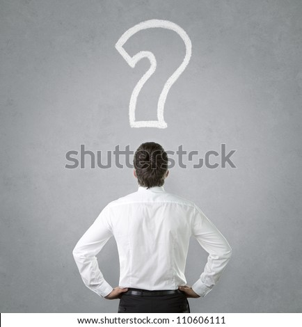 Confused, young businessman looking at question mark - stock photo
