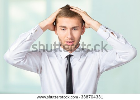 Confused young businessman thinking