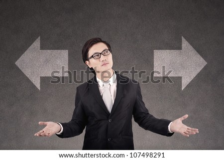 Confused young businessman with two sign of business choices - stock photo