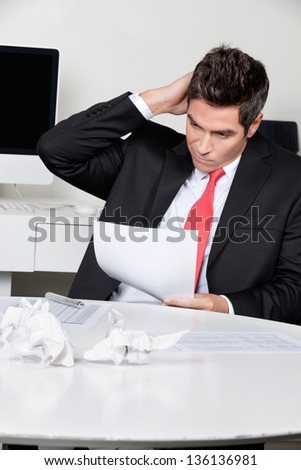 Confused young businessman working at desk in office - stock photo