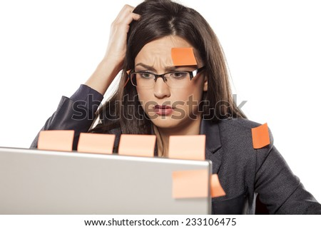 confused young businesswoman with stickers on her and her laptop - stock photo