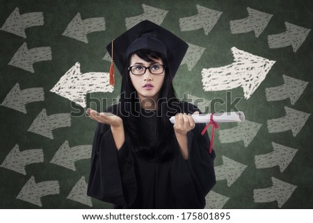 Confused young female in graduation gown with arrow symbol on the blackboard - stock photo