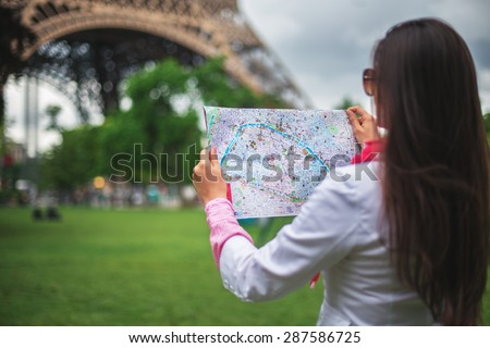 Confused young girl holding city Maps in Tuileries garden Paris, France - stock photo