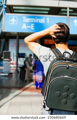 Confused young man with backpack looking for right direction in airport - stock photo