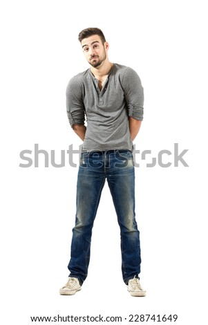 Confused young man with raised shoulders. Full body length isolated over white background. - stock photo
