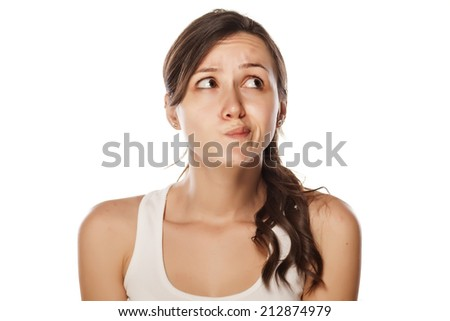 confused young woman posing on a white background - stock photo