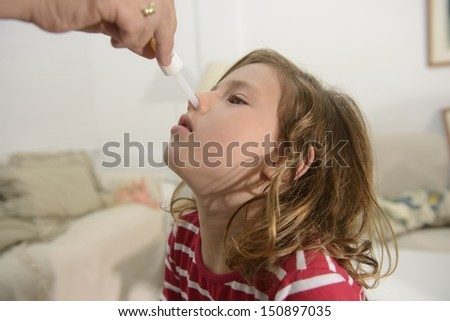 Congested nose: Mom applying nose drops - stock photo