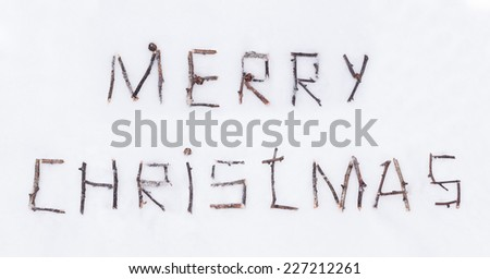 Congratulation text merry christmas written with broken wooden sticks on snow background in rustic style - stock photo