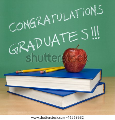 Congratulations graduates written on a chalkboard. Books, pencils and an apple on foreground. - stock photo