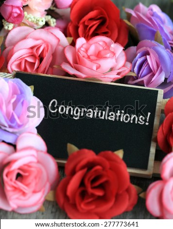 congratulations message on chalkboard, with flowers in background - stock photo