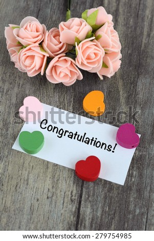 congratulations message, with flowers and wooden background - stock photo