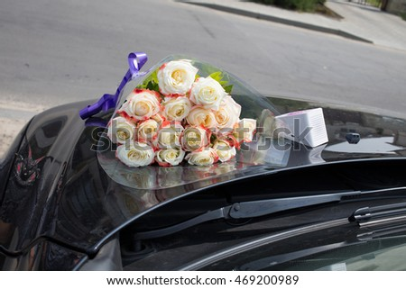 Congratulations to the event. There are a bouquet of roses and wi-fi speaker on the hood of a black car.