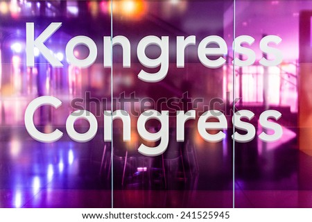 Congress room: Glass wall with German and English wording for congress with seats in the background - stock photo