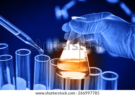 Conical flask in scientist hand with dropping chemical liquid to test tube  - stock photo