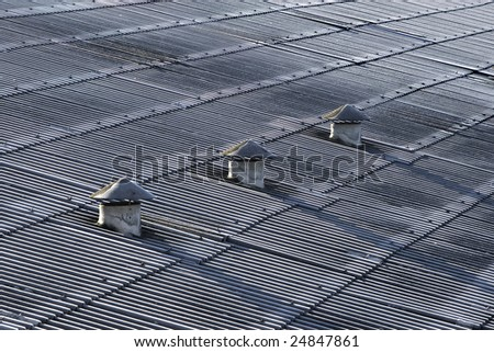 Conical vent chimneys on a rooftop of an old warehouse. - stock photo