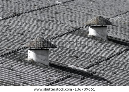 Conical vent chimneys on asbestos rooftop of an old warehouse.(Concept of public health danger) - stock photo