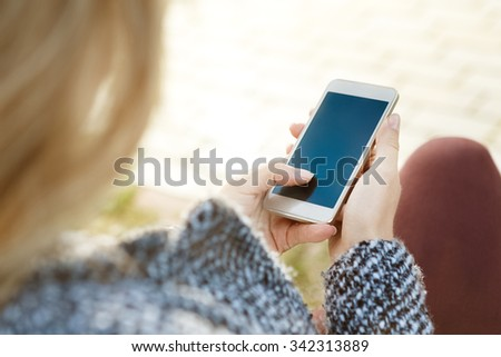 Connected anywhere at any time. Top view cropped shot of a woman holding phone in her hands  - stock photo