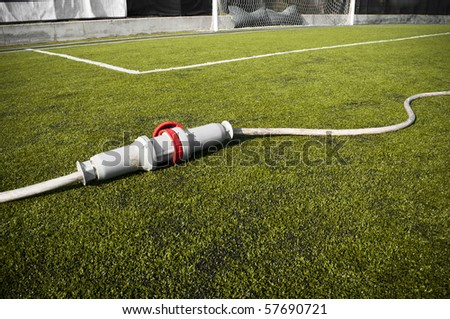 Connected wire in a soccer field on grass - stock photo