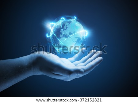 Connected World. Conceptual business  illustration. A man holding a glowing projection of the world. - stock photo
