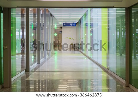 Connecting corridor in green glass hall - stock photo