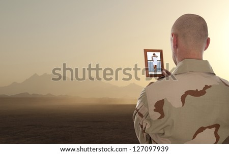 Conscript  marine looks at the photo of the girlfriend - stock photo