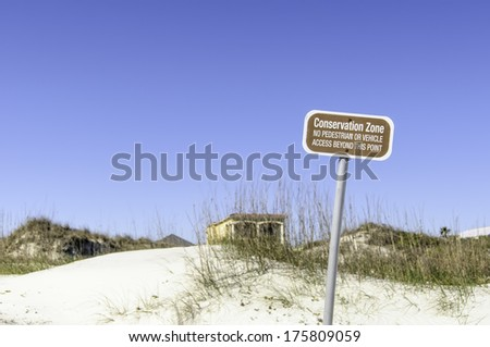 """Conservation sign on dune at beach near St. Augustine, Florida, USA: """"Conservation Zone / No pedestrian or vehicle access beyond this point"""" (selective focus) - stock photo"""