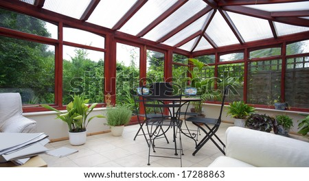 conservatory tables chairs plants room in house next to garden - stock photo